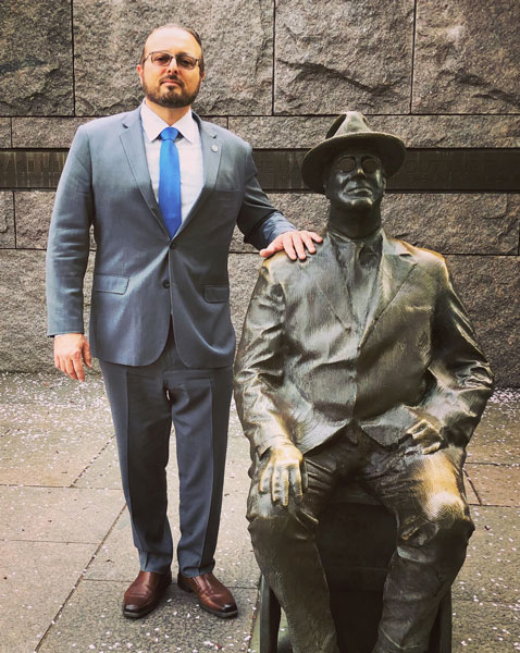 David Bini standing next to FDR statue