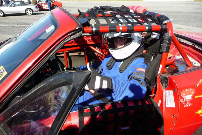 Jon in helmet in red race car