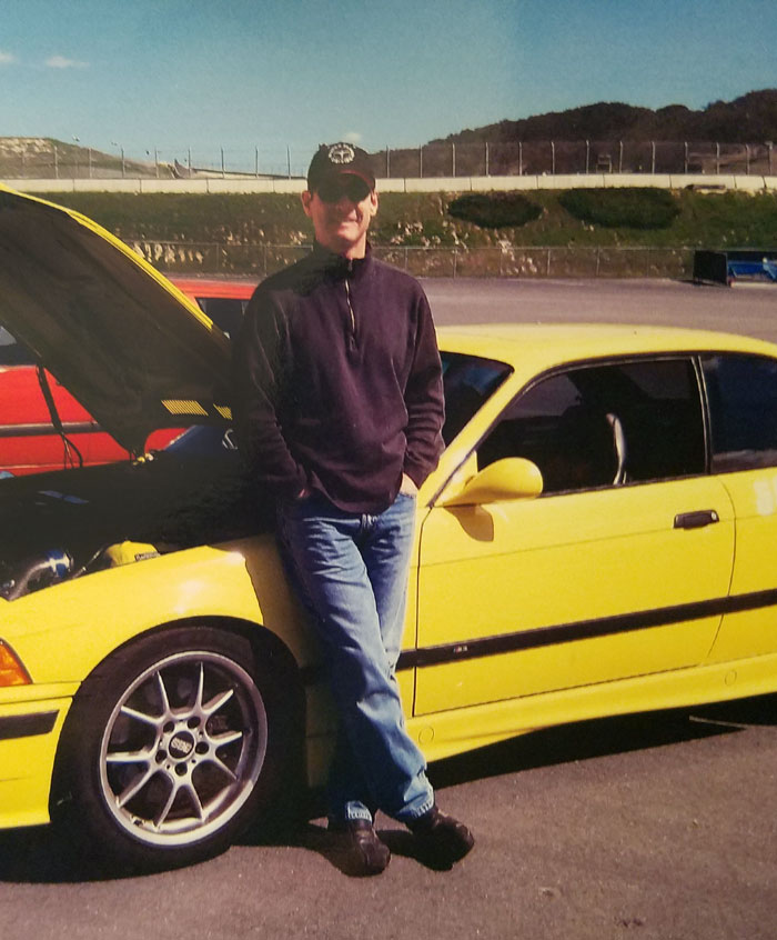 Jon leaning against yellow M3